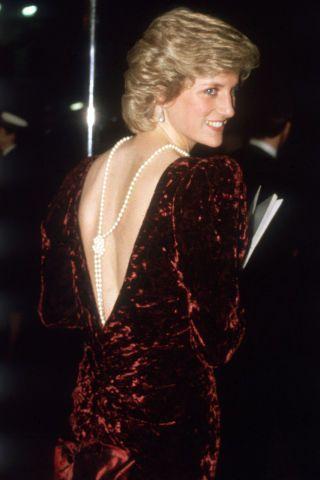 Pérolas adornam o decote profundo do vestido de veludo vinho