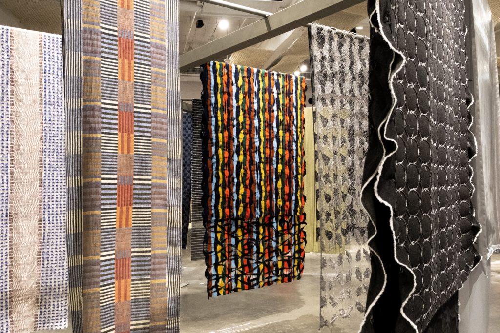 Foto de ambiente com grandes painéis de tecidos sustentáveis  pendurados.