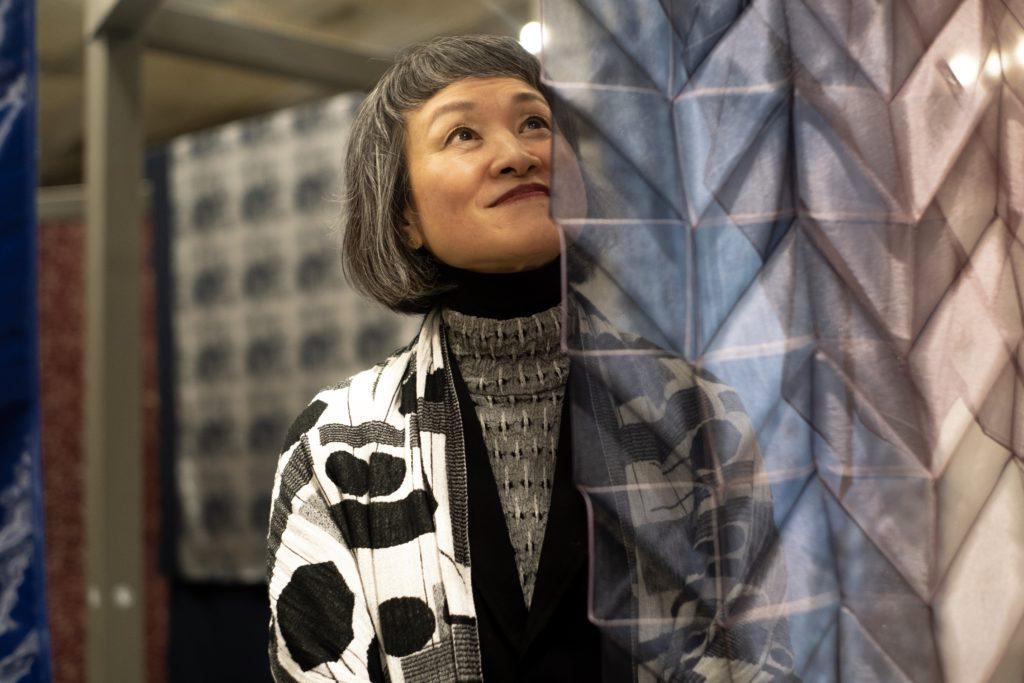 Fotografia mostra mulher japonesa olhando para um tecido transparente com textura. Outros tecidos aparecem ao fundo.