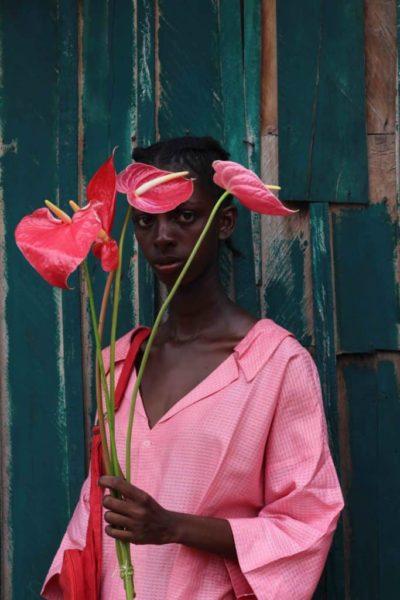 Retrato de modelo negra usando roupa rosa e segurando hastes de antúrios