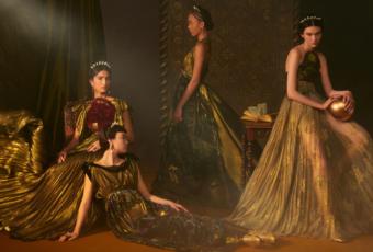 Quatro modelos com vestidos longos em tons de dourado, da Dior, contra um fundo escuro
