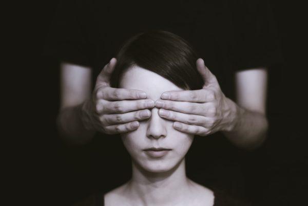 Imagem em preto e branco de uma mulher jovem cujos olhos estão tampados pelas mãos de outra pessoa, que está atrás dela.