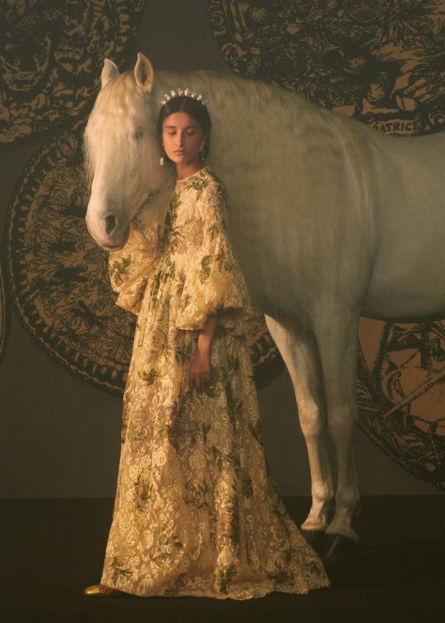 Uma modelo com vestido luxuoso de renda está de pé ao lado de um cavalo branco