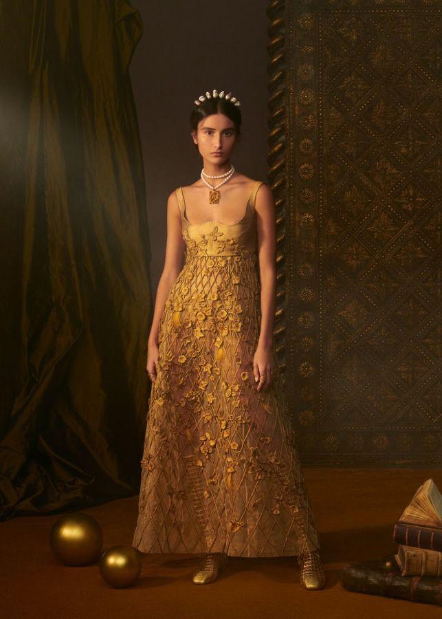 Modelo usando um vestido longo, dourado, em pé contra um fundo escuro